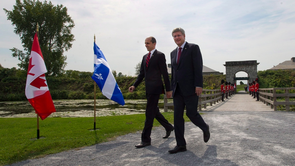 Prime Minister Stephen Harper, right, and Veteran's Affairs Minister Steven Blaney walk past an honour guard at Fort Lennox in Saint-Paul-de-L'ile-aux-Nois, Que. on Friday, September 14, 2012. (Ryan Remiorz / The Canadian Press)