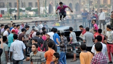 An Egyptian protester stomps on the roof of a car in Tahrir Square in Cairo, Egypt