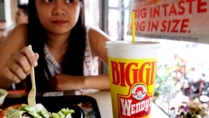 Pearl Ganotisi sips from her 24-ounce of soda drinks as she takes her meal in an American hamburger chain Friday, June 1, 2012 in Manila, Philippines (AP / Pat Roque)