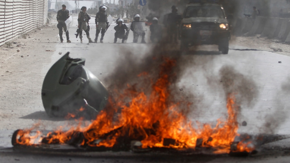 Afghan police stand by burning tires during a protest, in Kabul, Afghanistan, Monday, Sept. 17, 2012. (AP / Ahmad Jamshid)