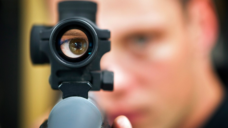 Patrick Deegan, a senior range officer at the Shooting Edge, looks through the scope of long gun at the store in Calgary, Wednesday, Sept. 15, 2010. (Jeff McIntosh / THE CANADIAN PRESS)