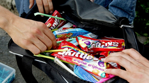 Grade 11 students open a bag containing candy they sell outside Moscrop Secondary School in Burnaby, B.C., on Wednesday, Sept. 17, 2008. (Darryl Dyck / THE CANADIAN PRESS)