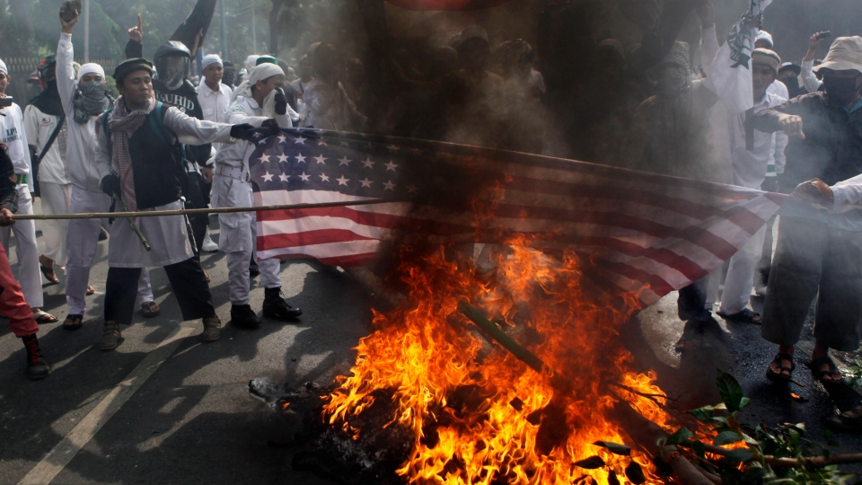 Muslim protesters burn a U.S. flag during a protest against American-made film 'Innocence of Muslims' that ridicules Islam and depicts the Prophet Muhammad as a fraud, a womanizer and a madman, outside the U.S. Embassy in Jakarta, Indonesia on Monday, Sept. 17, 2012. (AP /Dita Alangkara)