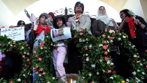 Libyans and Americans stand with wreaths, a poster and a photo of U.S. Ambassador Chris Stevens