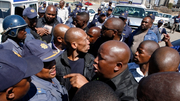 Firebrand politician Julius Malema, right argues with police officers, at Lonmin Platinum Mine
