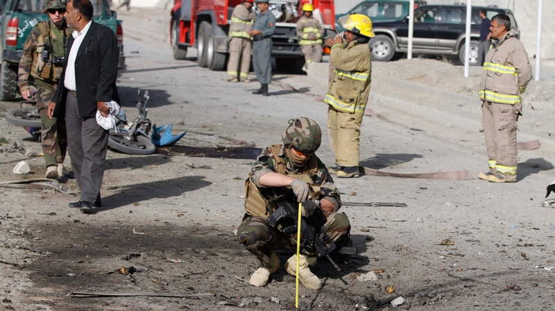 A French soldier investigates the scene of a suicide bombing, Tuesday, Sept. 18, 2012 in Kabul, Afghanistan. (AP Photo/Ahmad Jamshid)
