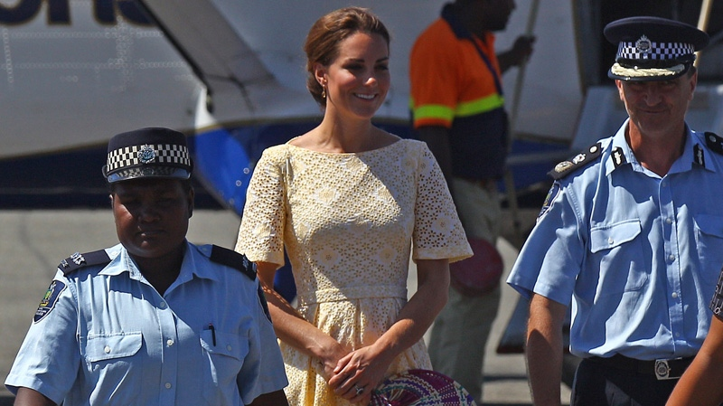 Kate, the Duchess of Cambridge, centre, walks with police as she and Prince William prepare to depart at the international airport in Honiara, Solomon Islands, Tuesday, Sept. 18, 2012, after an official visit to the South Pacific Island Nation. (AP / Rick Rycroft)