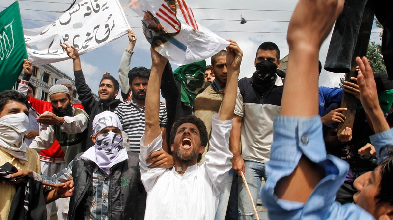 Kashmiri Muslim protesters burn a flag representing the U.S. and Israel as they shout slogans during a protest in Srinagar, India, Tuesday, Sept. 18, 2012. (AP Photo/Mukhtar Khan)