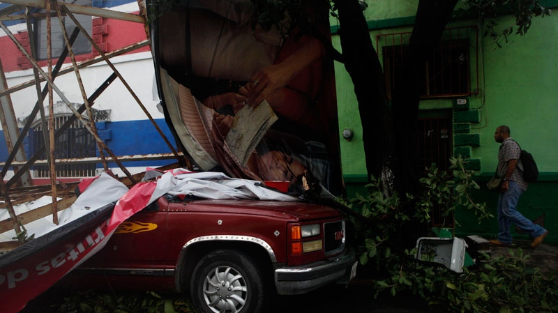 A man walks past a vehicle damaged by a fallen billboard after the passage of Hurricane Karl in Veracruz, Mexico, Friday, Sept. 17, 2010. Karl smashed into Mexico's Gulf Coast on Friday, killing at least two people and forcing the country to shut down its only nuclear power plant and its central Gulf Coast oil platforms. (AP / Alexandre Meneghini)