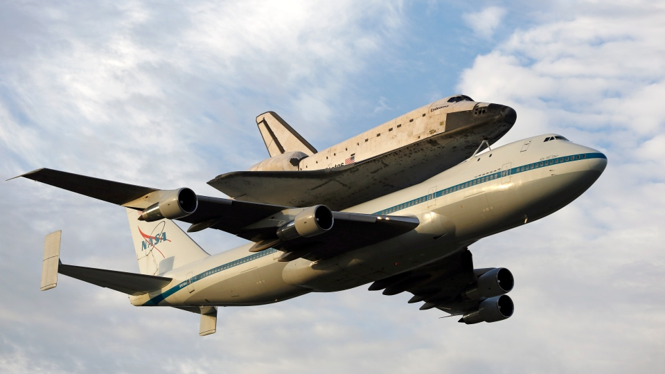 Space shuttle Endeavour, bolted atop a modified jumbo jet, makes its departure from the Kennedy Space Center, Wednesday, Sept. 19, 2012, in Cape Canaveral, Fla. (AP / Terry Renna)