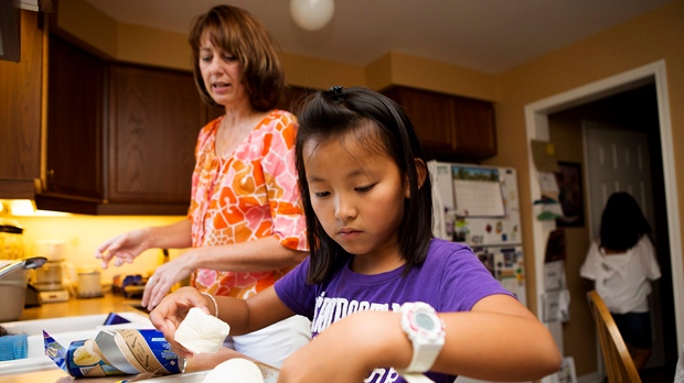 Lianne Thompson, left, and one of her adopted daughters, Cassidy Thompson, right, prepare dinner at their home in Mississauga on Wednesday, Sept. 5, 2012. (Michelle Siu / THE CANADIAN PRESS)
