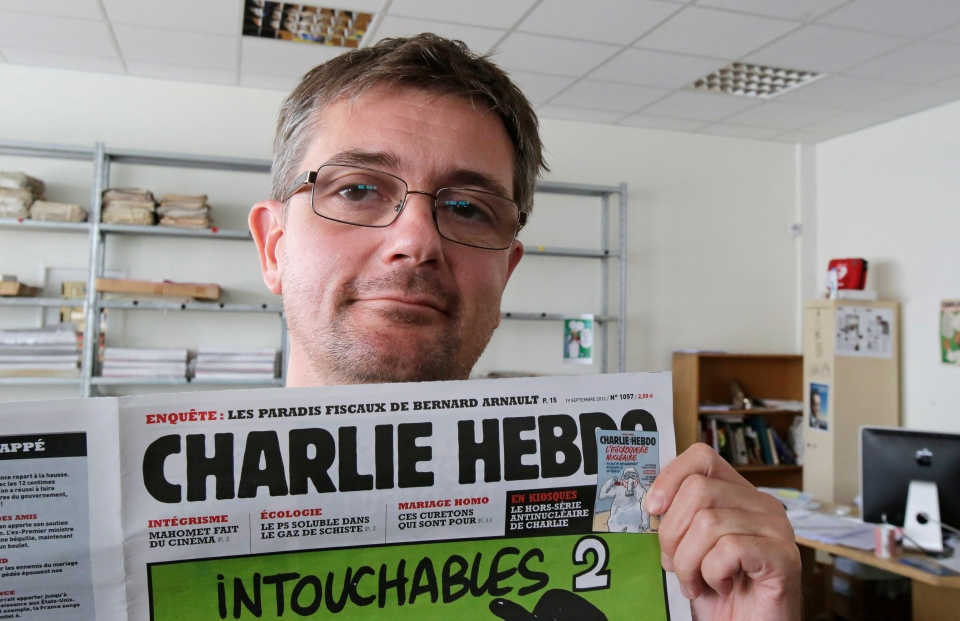 Publishing director of the satyric weekly Charlie Hebdo, Charb, displays the front page of the newspaper as he poses for photographers in Paris, Wednesday, Sept. 19, 2012. (AP / MIchel Euler)