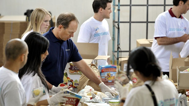 Citi Canada CEO John Hastings, left blue shirt, helps some of his 80 employees sort food at the Daily Bread Food Bank in Toronto on Saturday, June 16, 2012. (Citi/The Canadian Press)