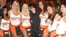 Hooters Girls Anisa, left to right, Kristi, Caitlin, Tania, Mandy and Courtney pose for a photo with singer Justin Bieber at the West Edmonton Mall Hooters on Saturday Sept. 18, 2010.  (Hooters Restaurant- Les Johansen)