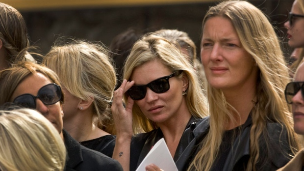 British model Kate Moss, centre, adjust her sunglasses as she listens to Scottish bagpipers playing outside the memorial service for Alexander McQueen at St Paul's Cathedral in London, which takes place during London Fashion Week, in London, Monday, Sept. 20, 2010. (AP / Joel Ryan)