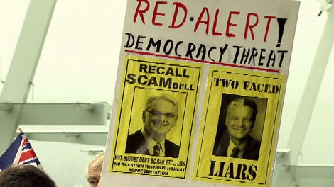 An anti-HST protester holds a poster calling for recall campaigns targeting Premier Gordon Campbell and Finance Minister Colin Hansen. Sept. 20, 2010. (CTV)