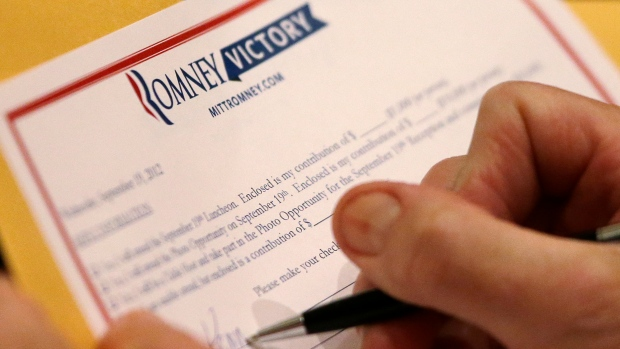 A donor fills out a contribution form for Mitt Romney