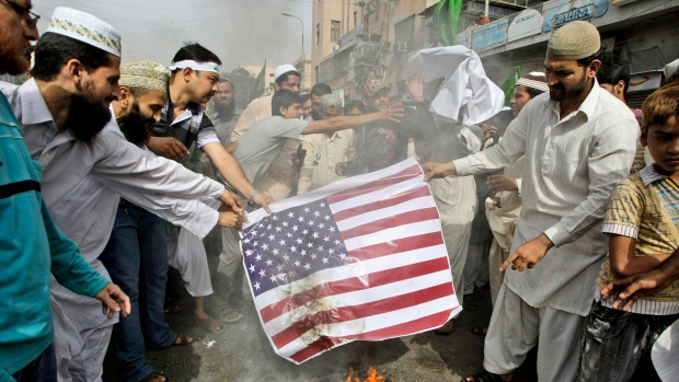 Pakistani supporters of Jamaat-e-Ahle-e-Sunnat burn a representation of a U.S. flag during a demonst