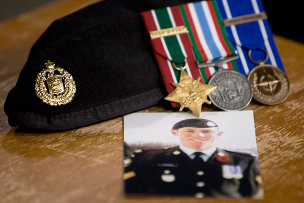 A photo of Cpl. Stuart Langridge is seen along with his beret and medals on a table during a news conference on Parliament Hill in Ottawa on Oct. 28, 2010. (Adrian Wyld / THE CANADIAN PRESS)