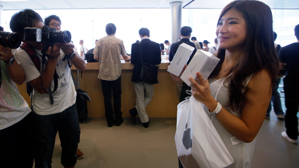 A customer shows her new iPhone 5 at the Apple store in Hong Kong Friday, Sept. 21, 2012. (AP / Kin Cheung)