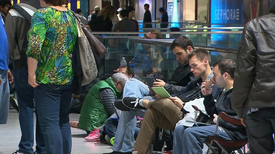 Customers wait in line to purchase the new iPhone 5 smartphone at the Apple Store in the Eaton Centre in Toronto, early Friday, Sept. 21, 2012.
