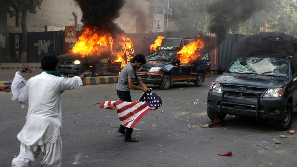 A protester carries a representation of a U.S. flag as police vehicles burn in Karachi, Pakistan on Friday, Sept 21, 2012. (AP / Fareed Khan)