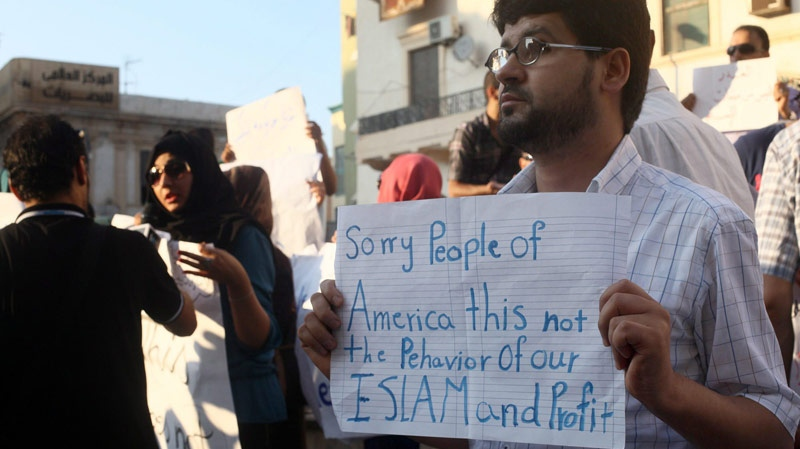 A Libyan man holds a placard in English during a demonstration against the attack on the U.S. consulate that killed four Americans in Benghazi, Libya, Wednesday, Sept. 12, 2012. (AP / Ibrahim Alaguri)