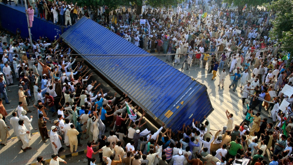 Pakistani protesters topple a shipping container police used to block the road to the US consulate in Lahore, Pakistan on Friday, Sept 21, 2012. (AP/K.M. Chaudary)