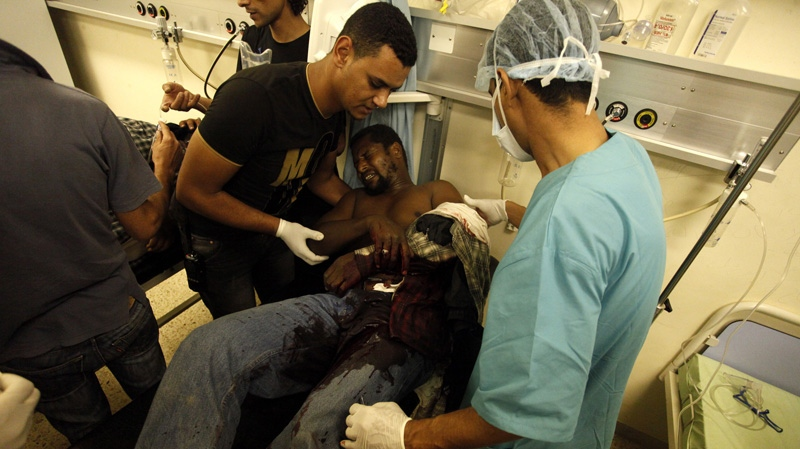 Libyan doctors at Benghazi Medical Centre help a Libyan civilian who was shot in his arm and his gut during a raid on armed Islamic militias compounds in Benghazi, Libya, Saturday, Sept. 22, 2012.  (AP Photo/Mohammad Hannon)