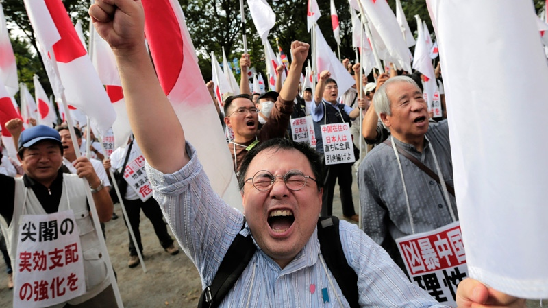 Japanese protesters shout slogans during a rally, opposing China's territorial claim over the disputed islands, called Senkaku in Japan and Diaoyu in China, at a park in Tokyo, Saturday, Sept. 22, 2012. (AP Photo/Itsuo Inouye)