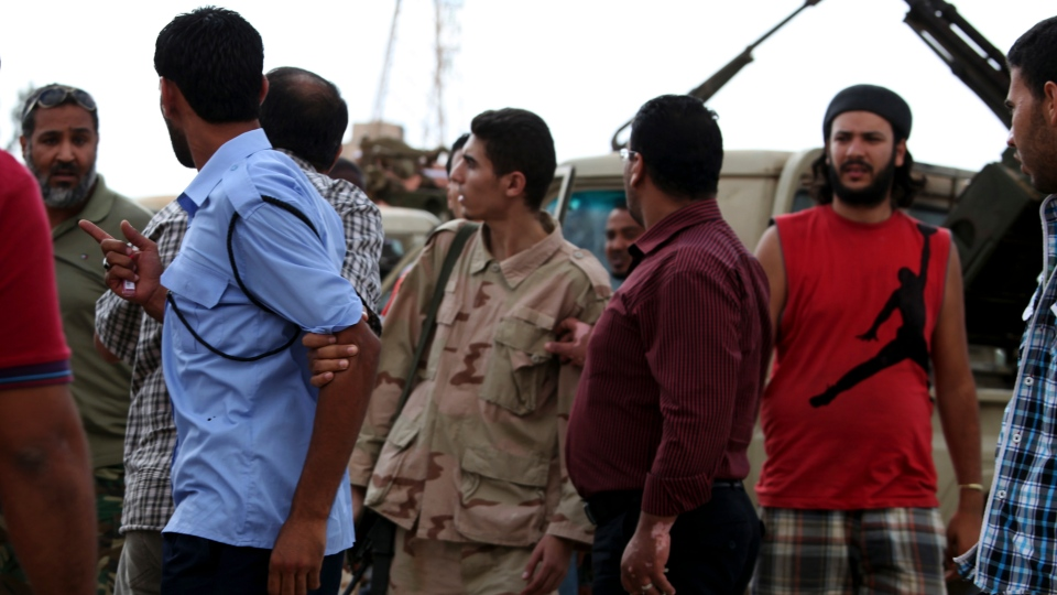 Members of the Rafallah Sahati Islamic Militia Brigades, argue with a Libyan policemen, second left, regarding a request for the militia to evacuate their base in Benghazi, Libya on Saturday, Sept. 22, 2012.(AP /Mohammad Hannon)
