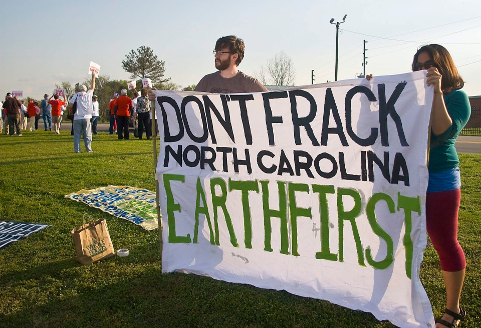 Protesters Todd Civilos, left, and Melin Mukherjee, right, with Croatan Earth First, hold up a sign against fracking during a public meeting on natural gas drilling at the Dennis A. Wicker Civic Center in Sanford, N.C. on Tuesday, March 20, 2012 . (AP /The Sanford Herald, Wesley Beeson)
