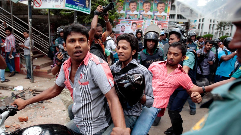 Bangladeshi policemen detain commuters on a motorbike after a clash between police and activists of an Islamic group during a protest in Dhaka, Bangladesh, Saturday, Sept. 22, 2012.  (AP /A.M. Ahad)
