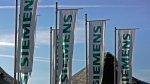 In this Jan. 24, 2008 file photo flags with the logo of industrial conglomerate Siemens AG  fly in front of the Olympic Hall in Munich, southern Germany. (AP Photo/Diether Endlicher, file)