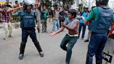 Bangladeshi policemen detain an activist of an Islamic group during a protest in Dhaka