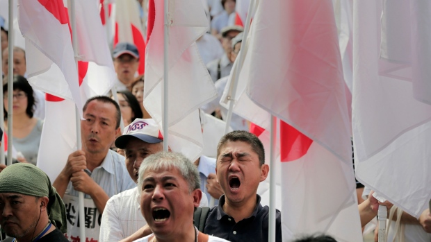 Protesters holding Japanese national flags shout slogans during a rally
