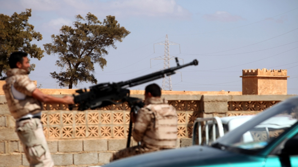 Soldiers from the Libyan National Army get ready to enter Rafallah al-sahati Islamic Militia Brigades compound, one of the compound buildings which can be seen behind the wall, in Benghazi, Libya, Saturday, Sept. 22, 2012.  (AP Photo/Mohammad Hannon)
