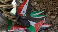 A Free Syrian Army Al-Faruk brigade fighter steps on Baath party and Syrian flags on Sept. 22, 2012.