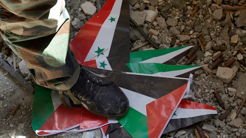 A Free Syrian Army fighter from the Al-Faruk brigade, steps on the Baath party and Syrian flags at Tal Abyad, a Turkish-Syrian border crossing captured by the rebels earlier in the week, eastern Syria, Saturday Sept. 22, 2012.  (AP / Hussein Malla)