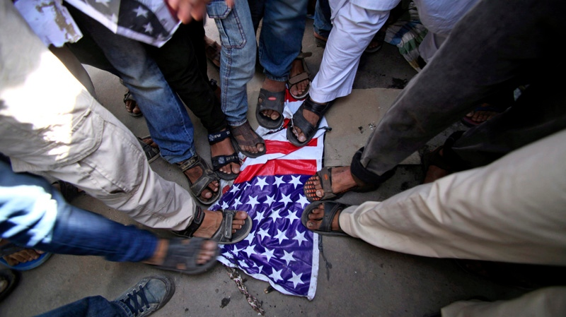 FILE - Indian Muslims stamp on a U.S. flag during a protest rally against an anti-Islam film called 'Innocence of Muslims' that ridicules Islam's Prophet Muhammad, in Jammu, India, Friday, Sept. 21, 2012. (AP/Channi Anand)