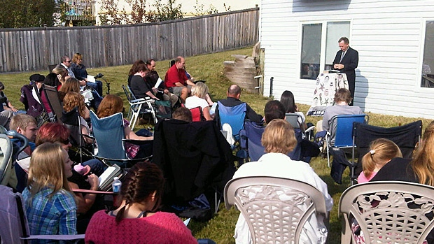 Members of the Morinville Baptist Church gather in a backyard for Sunday service, after their church building was completely destroyed by a fire on Saturday.