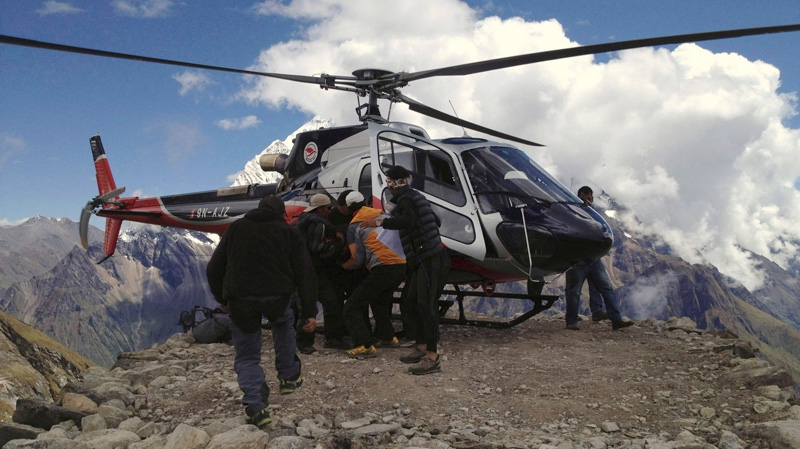 In this photo provided by Nepalese airline Simrik Air, an injured victim of an avalanche is carried to a helicopter after being rescued at the base camp of Mount Manaslu in northern Nepal, Sunday, Sept. 23, 2012.  (AP Photo/Simrik Air)
