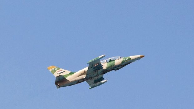A Syrian army jet is seen after attacking a residential area in Aleppo, Syria on Sept. 23, 2012.