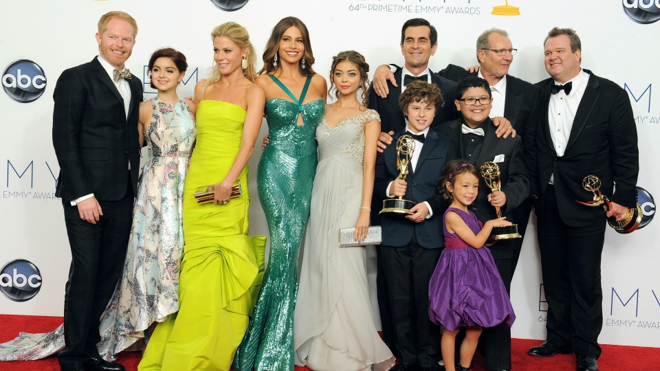The cast of 'Modern Family,' from left, Jesse Tyler Ferguson, Ariel Winter, Julie Bowen, Sofía Vergara, Sarah Hyland, Ty Burrell, background, Nolan Gould, Ed O'Neill, background second left, Rico Rodriguez, Aubrey Anderson-Emmons, foreground purple dress, and Eric Stonestreet, right, winners of the best outstanding comedy series, pose backstage at the 64th Primetime Emmy Awards at the Nokia Theatre on Sunday, Sept. 23, 2012, in Los Angeles. (Jordan Strauss / Invision)