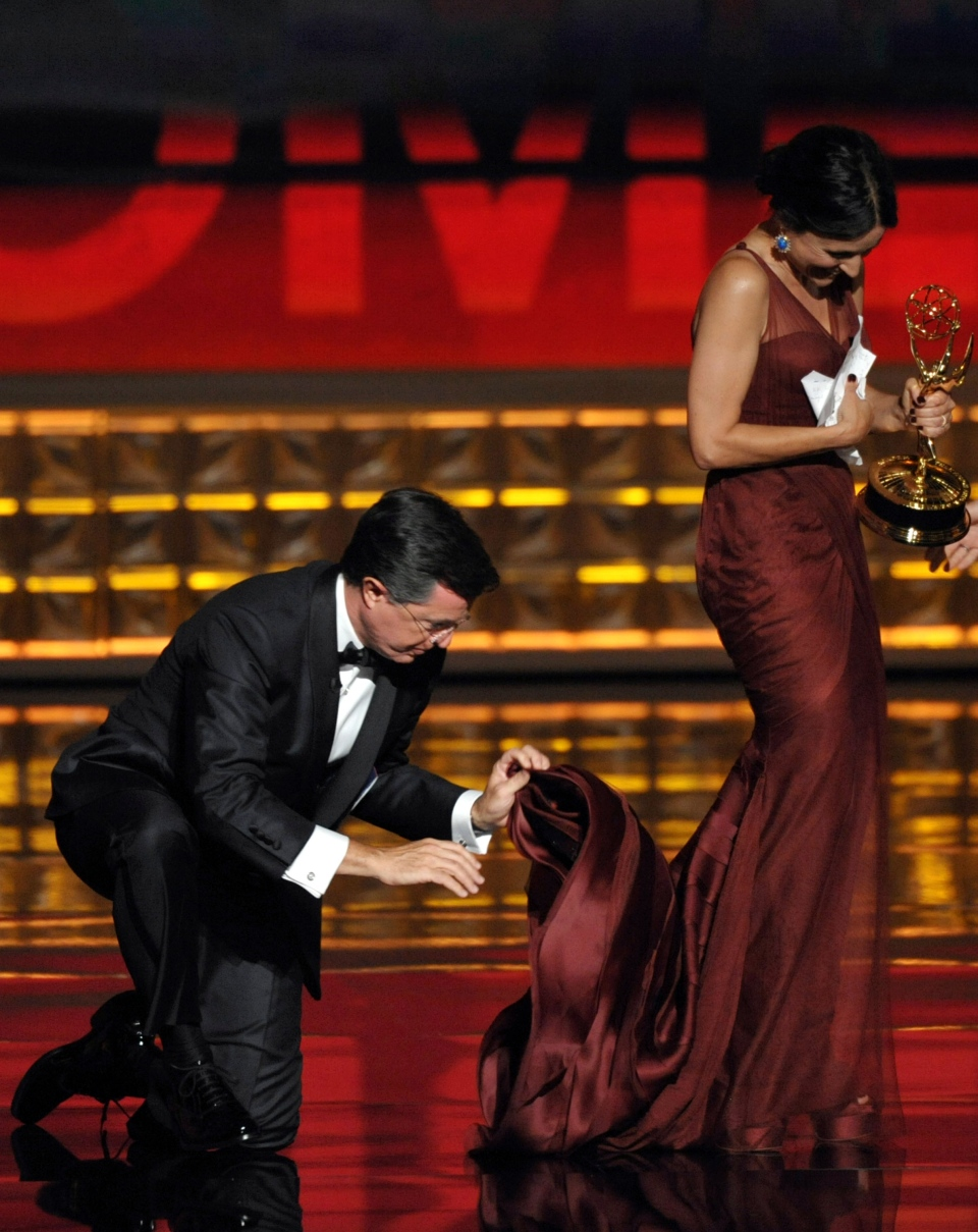 Stephen Colbert, left, holds on to the dress of Julia Louis-Dreyfus as she accepts the award for Outstanding Lead Actress in a Comedy Series for 'Veep' at the 64th Primetime Emmy Awards at the Nokia Theatre on Sunday, Sept. 23, 2012, in Los Angeles. (John Shearer / Invision)