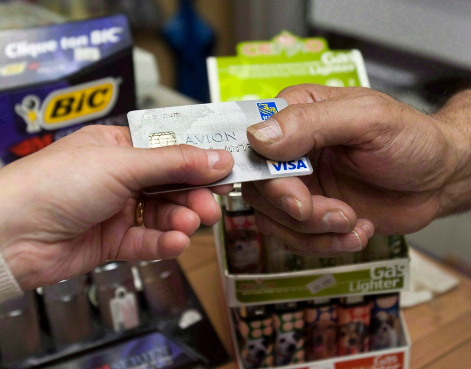 A consumer pays with a credit card at a store in Montreal July 6, 2010. (Ryan Remiorz / THE CANADIAN PRESS)