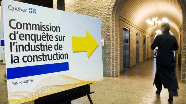 A woman walks by a sign pointing towards a security checkpoint in Montreal, Monday, June 4, 2012 at a Quebec inquiry looking into allegations of corruption in the province's construction industry. (THE CANADIAN PRESS/Graham Hughes)
