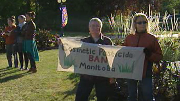 A group holds a sign to protest the use of cosmetic pesticides in Manitoba.