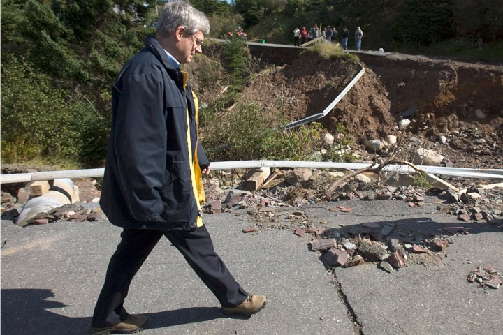 Prime Minister Stephen Harper walks on a washed-out road during a visit to Britannia, Newfoundland and Labrador on Friday, Sept. 24, 2010. (Andrew Vaughan / THE CANADIAN PRESS)