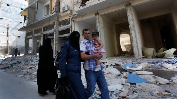 A Syrian family walk past a destroyed street that was attacked by a Syrian government airstrike earlier in the day at al-Shaar neighborhood, in Aleppo city, Syria, Monday Sept. 24, 2012.  Read more: http://www.ctvnews.ca/world/1-5-million-syrians-need-food-aid-up-from-250-000-in-april-un-1.968702#ixzz2EIknnJMh